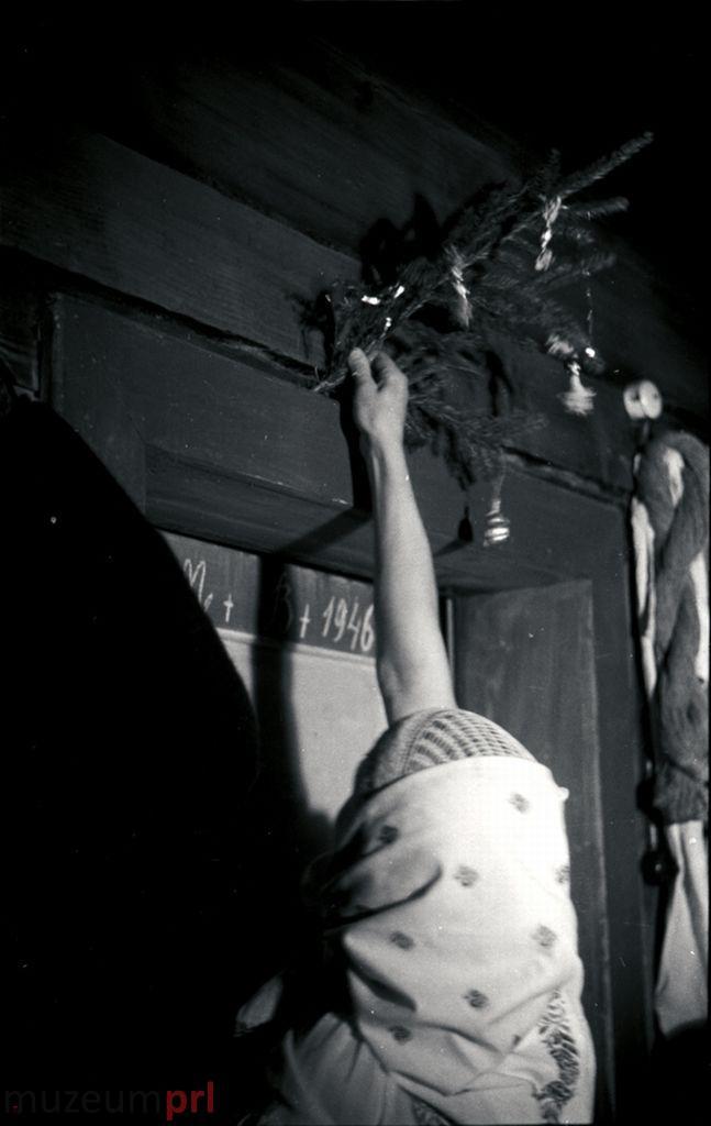 wizerunek  Istebna. Gospodyni wieszająca połaźniczkę nad drzwiami wejściowymi.