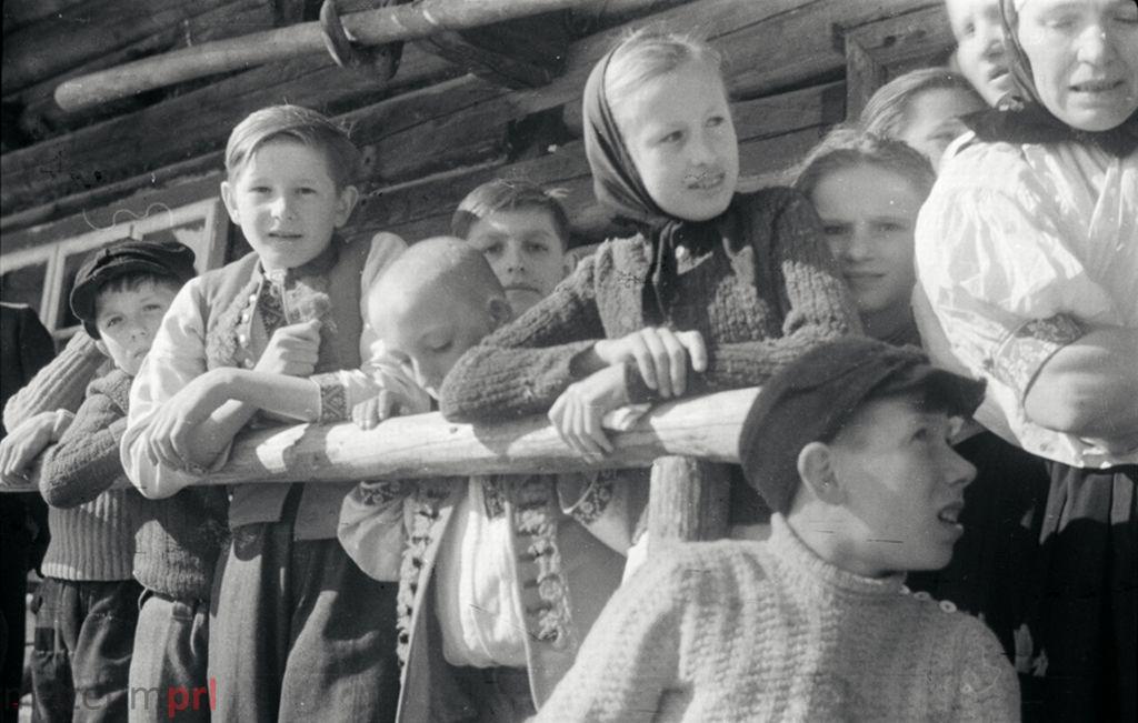 wizerunek  Istebna. Grupa wiejskich dzieci na werandzie przed góralską chatą.