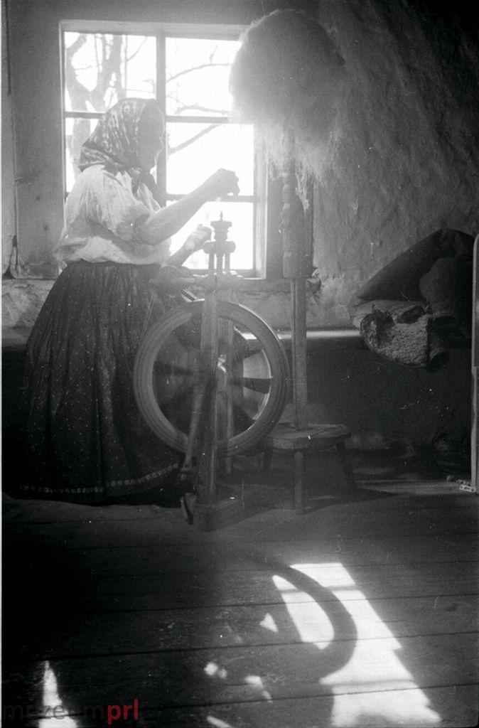 wizerunek  Istebna. Starsza kobieta przy kołowrotku.