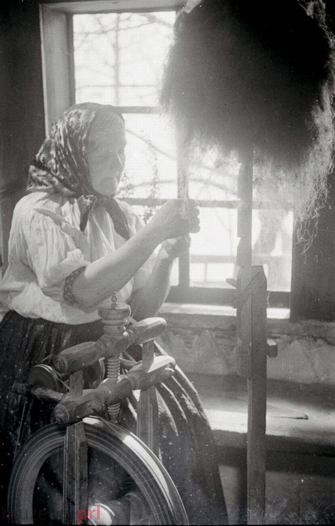 wizerunek  Istebna. Zbliżenie na starszą kobietę przy kołowrotku.